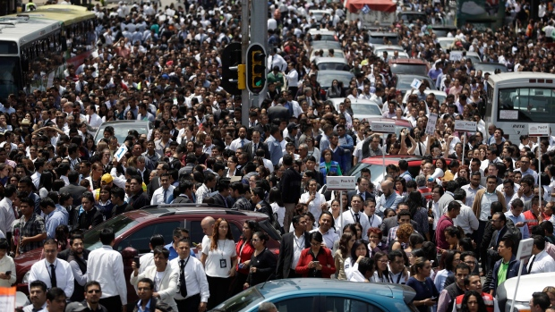 People evacuated from office buildings gather in Reforma Avenue after an earthquake in Mexico City, Tuesday Sept. 19, 2017. (AP Photo / Rebecca Blackwell)
