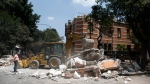 A bulldozer removes debris from a partially collapsed building after an earthquake in Mexico City, Tuesday, Sept. 19, 2017. (AP Photo / Rebecca Blackwell)