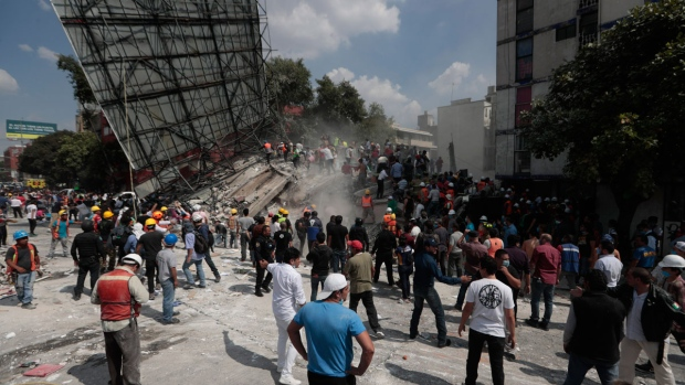 Rescue workers and volunteers search a building that collapsed after an earthquake in the Roma neighborhood of Mexico City, Tuesday, Sept. 19, 2017. A powerful earthquake jolted central Mexico on Tuesday, causing buildings to sway sickeningly in the capital on the anniversary of a 1985 quake that did major damage. (Eduardo Verdugo/AP)