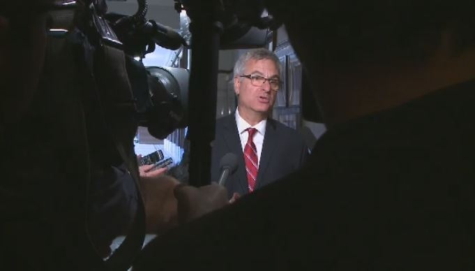 Government House Leader Jean-Marc Fournier meets a throng of reporters at the National Assembly.