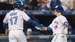 Toronto Blue Jays' Darwin Barney, right, is congratulated by Ryan Goins after driving him in with a two-run home run in the sixth inning of their American League MLB baseball game against the Kansas City Royals in Toronto on Tuesday, September 19, 2017. (THE CANADIAN PRESS/Fred Thornhill)