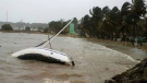 A boat lays on its side off the shore of Sainte-Anne on the French Caribbean island of Guadeloupe, early Tuesday, Sept. 19, 2017, after the passing of Hurricane Maria. (AP Photo/Dominique Chomereau-Lamotte)