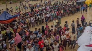 Rohingya Muslim men, who crossed over from Myanmar into Bangladesh, wait for their turn to collect food aid near Kutupalong refugee camp, Bangladesh, Tuesday, Sept. 19, 2017. With a mass exodus of Rohingya Muslims sparking accusations of ethnic cleansing from the United Nations and others, Myanmar leader Aung San Suu Kyi on Tuesday said her country does not fear international scrutiny and invited diplomats to see some areas for themselves. (AP Photo/Dar Yasin)