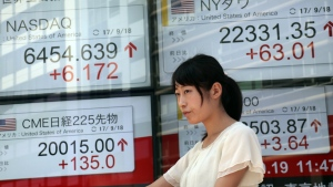 A woman walks past an electronic stock indicator of a securities firm in Tokyo, Tuesday, Sept. 19, 2017. (AP / Shizuo Kambayashi)