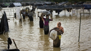 Rohingya Muslims, who crossed over recently from Myanmar into Bangladesh, carry their belongings and leave their flooded camp for alternate shelter near Balukhali refugee camp in Cox's Bazar, Bangladesh on Tuesday, Sept. 19, 2017. (AP / Bernat Armangue)