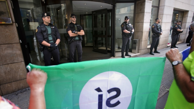 Guardia Civil officers stand guard at the entrance of the Department of External Affairs, Institutional Relations and Transparency of the Catalan Government office in Barcelona, Spain on Wednesday, Sept. 20, 2017. (AP / Emilio Morenatti)