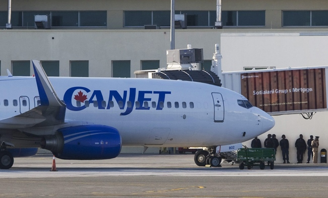 Soldiers stand near the hijacked CanJet 737 as it sits on the tarmac at the airport in Montego Bay, Jamaica, Monday, April 20, 2009. (Adrian Wyld / THE CANADIAN PRESS)