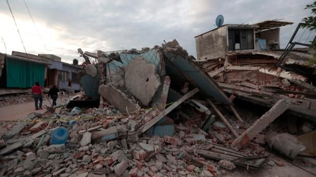 Residents walk past buildings demolished by a 7.1 earthquake, in Jojutla, Morelos state, Mexico, Wednesday, Sept. 20, 2017. (AP Photo/Eduardo Verdugo)