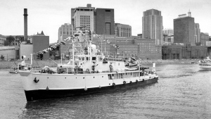 In this Sept. 10, 1983 file photo, Jacques Cousteau's research vessel, the Calypso, makes its way past downtown St. Paul to a berth at Harriet Island, Minnesota. (AP Photo/IS, file)