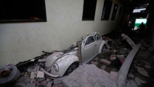 A car sits crushed from a building felled by a 7.1 earthquake, in Jojutla, Morelos state, Mexico, Wednesday, Sept. 20, 2017. (AP / Eduardo Verdugo)