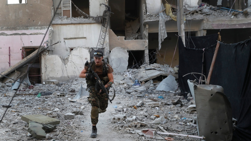 In this July 27, 2017 file photo, a U.S.-backed Syrian Democratic Forces fighter runs in front of a damaged building as he crosses a street on the front line, in Raqqa, Syria. (AP Photo / Hussein Malla, File)