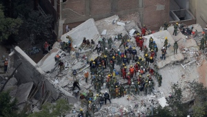 Rescue workers search for people trapped inside a collapsed building in the Condesa neighborhood of Mexico City, Wednesday, Sept. 20, 2017. Mexicans across the city are digging through collapsed buildings, trying to save people trapped in debris under schools, homes and businesses, toppled by a 7.1 earthquake that killed more than 200 people. (AP Photo/Rebecca Blackwell)