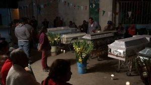 Mourners hold a wake for 11 family members who were killed inside the Santiago Apostol church during the 7.1 earthquake in the town of Atzala in Puebla state, Mexico, Wednesday, Sept. 20, 2017. (AP / Pablo Spencer)