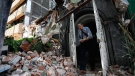 A man walks through a door frame of a building that collapsed during a 7.1 magnitude earthquake, in the Condesa neighborhood of Mexico City, Tuesday, Sept. 19, 2017. (AP Photo/Marco Ugarte)