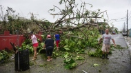 A family helps clean the road after HurricaneMaria hit the eastern region of the island, in Humacao, Puerto Rico, Tuesday, September 20, 2017. The strongest hurricane to hit Puerto Rico in more than 80 years destroyed hundreds of homes, knocked out power across the entire island and turned some streets into raging rivers in an onslaught that could plunge the U.S. territory deeper into financial crisis. (AP Photo/Carlos Giusti)