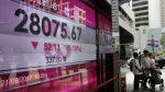 People walk past an electronic board showing Hong Kong share index outside a local bank in Hong Kong on Thursday, April 21, 2017. (AP / Vincent Yu)