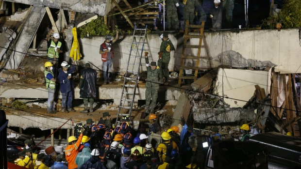 Rescue personnel work on the rescue of a trapped child at the collapsed Enrique Rebsamen primary school in Mexico City on Sept. 20, 2017. (AP / Marco Ugarte)