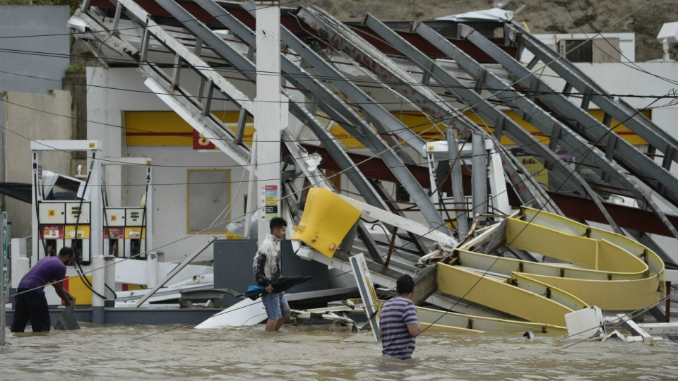 People walk next to a gas station flooded and damaged by the impact of Hurricane Maria, which hit the eastern region of the island, in Humacao, Puerto Rico on Wednesday, Sept. 20, 2017. (AP / Carlos Giusti)