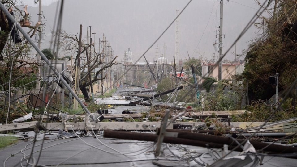 Electricity poles and lines lay toppled on the road after Hurricane Maria hit the eastern region of the island, in Humacao, Puerto Rico, Wednesday, Sept. 20, 2017. (AP Photo/Carlos Giusti)