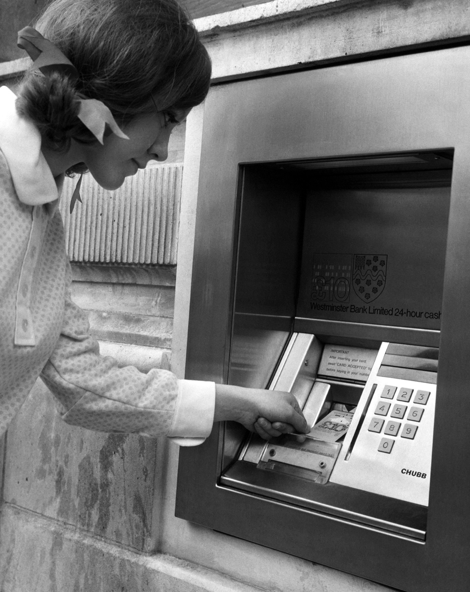 In this Jan. 19, 1968, file photo, a woman puts her computer punch card into the slot of an automated teller machine, outside a bank in central London. The first ATM was installed in London in 1967, with John Shepherd-Barron being credited with inventing the machine. (AP Photo/File)
