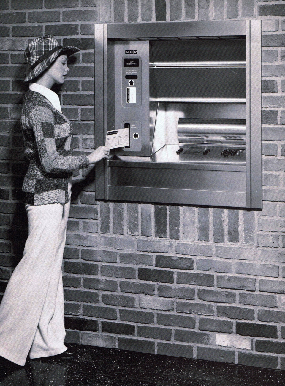 In this photo provided by NCR of an image from a 1974 company announcement, a woman uses an automated teller machine. (Courtesy of NCR via AP)