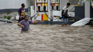 People walk next to a gas station flooded and damaged by the impact of Hurricane Maria, which hit the eastern region of the island, in Humacao, Puerto Rico, Wednesday, September 20, 2017. (AP Photo/Carlos Giusti)