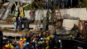 Rescue personnel work on the rescue of a trapped child at the collapsed Enrique Rebsamen primary schoool in Mexico City, Sept. 20, 2017. (AP Photo/Marco Ugarte)