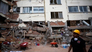 A rescue worker walks in front of an apartment building whose first four floors collapsed, in the Lindavista neighborhood of Mexico City, Wednesday, Sept. 20, 2017. People by the millions rushed from homes and offices across central Mexico, after a 7.1 earthquake, sometimes watching as buildings they had just fled fell behind them with an eruption of dust and debris. (AP Photo/Rebecca Blackwell)