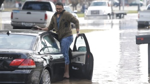 FILE - In this Jan. 18, 2017 file photo, Syed Ali waits with his stranded car after it flooded in Houston. Flash flood warnings are in effect for the Houston region, where torrential rains prompted officials to close some schools and delay opening many others on Wednesday. (Melissa Phillip/Houston Chronicle via AP)