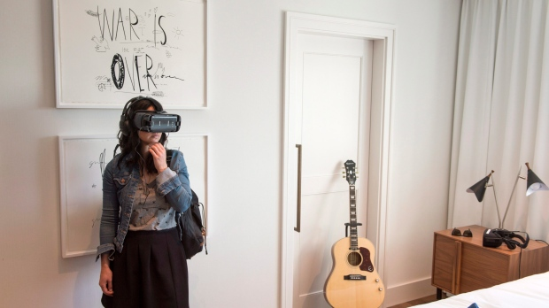 A woman dons a virtual-reality headset during the unveiling of a new design of the hotel suite made famous by John Lennon and Yoko Ono during their 1969 bed-in for peace, Thursday, September 21, 2017 in Montreal. (THE CANADIAN PRESS/Paul Chiasson)