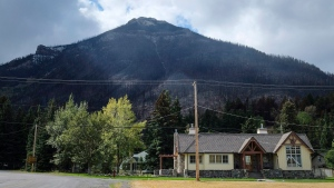 Houses are dwarfed by a burned mountainside in Waterton Lakes, Alta., Wednesday, Sept. 20, 2017. (THE CANADIAN PRESS / Jeff McIntosh)