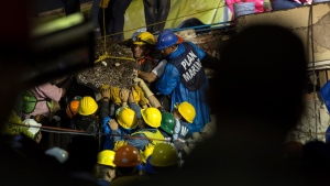 Search and rescue team members work to bring down a large piece of concrete during rescue efforts at the Enrique Rebsamen school in Mexico City, Mexico, Thursday, Sept. 21, 2017. (AP Photo/Anthony Vazquez)