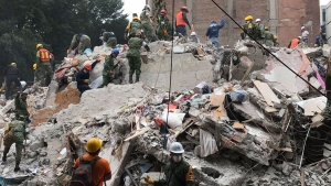 Rescue workers dig through rubble in an attempt to find survivors. (@PeterAkman/Twitter)