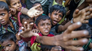 Rohingya Muslim children, who crossed over from Myanmar into Bangladesh, stretch out their arms out to collect chocolates and milk distributed by Bangladeshi men at Taiy Khali refugee camp, Bangladesh, on Thursday, Sept. 21, 2017.  (AP /Dar Yasin)