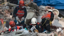 Rescue personnel look through a photo album as they work in rescue operations in the rubble of a building felled by a 7.1 magnitude earthquake, in the Ciudad Jardin neighborhood of Mexico City, Thursday, Sept. 21, 2017. Thousands of professionals and volunteers are working frantically at dozens of wrecked buildings across the capital and nearby states looking for survivors of the powerful quake that hit Tuesday. (Eduardo Verdugo/AP)