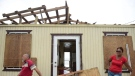 Julio Morales and Miriam Pagan stand on the front of their damaged home, in El Negro community a day after the impact of Hurricane Maria, Puerto Rico, Thursday, September 21, 2017. As of Thursday evening, Maria was moving off the northern coast of the Dominican Republic with winds of 120 mph (195 kph). The storm was expected to approach the Turks and Caicos Islands and the Bahamas late Thursday and early Friday. (Carlos Giusti/AP)
