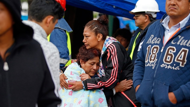 Family members embrace as they wait for news of their relatives outside a quake-collapsed seven-story building in Mexico City's Roma Norte neighborhood, Friday, Sept. 22, 2017. (AP / Rebecca Blackwell)