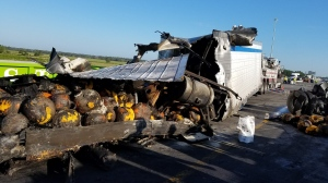 This photo provided by Florida Highway Patrol shows a truck carrying pumpkins after hitting a guard rail on I-75 near Tampa, Fla. The truck then exploded, spilling the burning pumpkins onto the highway. (Florida Highway Patrol via AP)