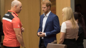 Prince Harry talks with Canadian veteran Mike Trauner, left, as Trauner's wife Leah Cuffe, right, and moderator Bronwen Evans look on during a reception before attending the True Patriot Love Symposium, in Toronto on Friday, September 22, 2017. THE CANADIAN PRESS/Chris Young