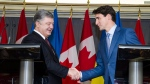 Prime Minister Justin Trudeau, right, and the President of Ukraine, Petro Poroshenko, shake hands after holding a press conference in Toronto on Friday, September 22, 2017. (THE CANADIAN PRESS / Christopher Katsarov)