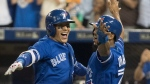 Toronto Blue Jays' Ryan Goins, left, celebrates his grand-slam against the New York Yankees with Richard Urena in the sixth inning in their American League MLB baseball game in Toronto on Friday, September 22, 2017. (THE CANADIAN PRESS/Fred Thornhill)