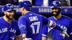 Toronto Blue Jays shortstop Ryan Goins (17) is congratulated by Kevin Pillar, left, and Jose Bautista after hitting a grand-slam against the New York Yankees during sixth inning AL baseball action in Toronto on Friday, September 22, 2017. (Frank Gunn/The Canadian Press)