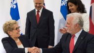 Ontario Premier Kathleen Wynne, left, and Quebec Premier Philippe Couillard shake hands after signing an agreement, at the end of a joint cabinet meeting between Quebec and Ontario, Friday, September 22, 2017 in Quebec City. Quebec Economy, Science and Innovation Minister Dominique Anglade, right, and Ontario Research and Innovation Minister Reza Moridi, centre, look on. THE CANADIAN PRESS/Jacques Boissinot