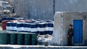 In this May 8, 2016, file photo, a North Korean solder stands guard near barrels stacked up near the river bank of the North Korean town of Sinuiju, opposite the Chinese border city of Dandong. (Chinatopix via AP, File)