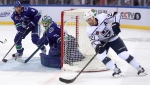 Los Angeles Kings' Trevor Lewis skates around the goal with the puck as the Vancouver Canucks' Chris Tanev, left, and goalie Anders Nilsson watch, during the third period of their NHL China exhibition hockey game at the Cadillac Arena in Beijing, Sept. 23, 2017. (Mark Schiefelbein/AP)