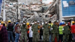 Soldiers stand next to a collapsed building where rescue workers race against the clock to reach possible survivors trapped inside a office building in the Roma Norte neighborhood of Mexico City, in the early morning hours of Sept. 23, 2017. (Rebecca Blackwell/AP)