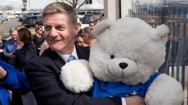 New Zealand Prime Minister Bill English embraces a National Party mascot while on the campaign trail in Cambridge, New Zealand, Friday, Sept. 22, 2017. (Mark Mitchell / New Zealand Herald)