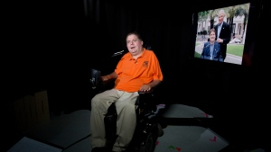 In this Tuesday, Sept. 19, 2017 photo, Marc Buoniconti talks during an interview in New York. On the right is a photograph of the former Citadel player with his father, Nick Buoniconti. Buoniconti wants to see youth football banned. (AP Photo/Mark Lennihan)