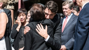 Prime Minister Justin Trudeau hugs the mother of former Liberal MP Arnold Chan during his funeral service in Toronto on Saturday, September 23, 2017. THE CANADIAN PRESS/Christopher Katsarov