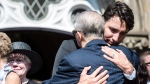 Prime Minister Justin Trudeau hugs the father of former Liberal MP Arnold Chan during his funeral service in Toronto on Saturday, September 23, 2017. (THE CANADIAN PRESS/Christopher Katsarov)